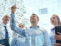 35772478-business-people-teamwork-and-planning-concept-smiling-business-team-with-marker-and-stickers-working-Stock-Photo